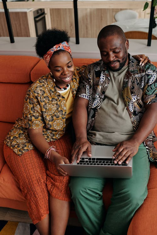 Couple Using Laptop While Sitting on Orange Couch