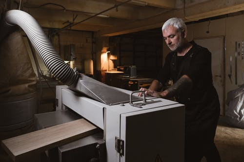 Thoughtful middle aged skillful male working with metal turning machine in spacious workshop