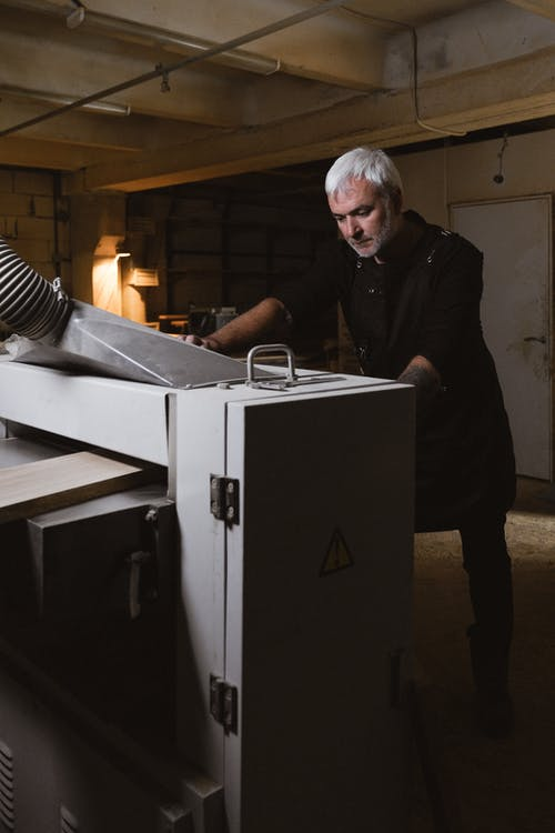 Middle aged man installing turning machine in workshop
