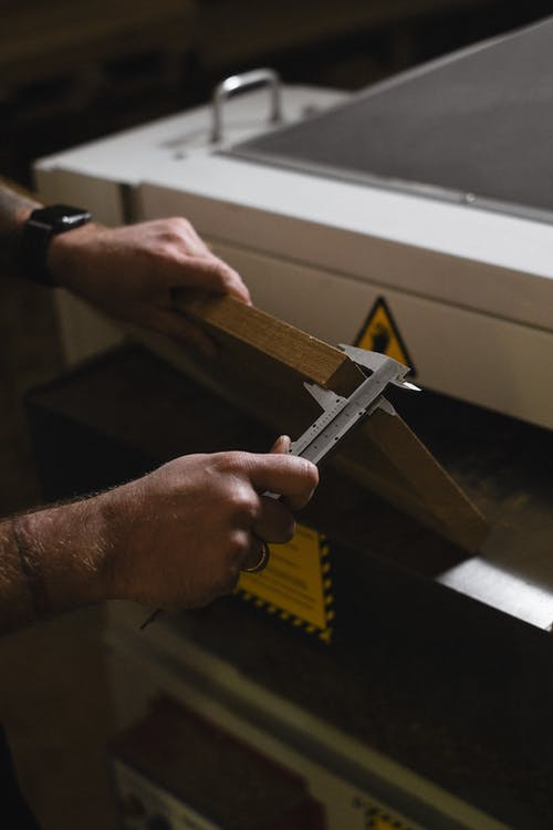 Unrecognizable male artisan using vernier caliper to measure wooden plank while standing near special machine in professional joinery during work