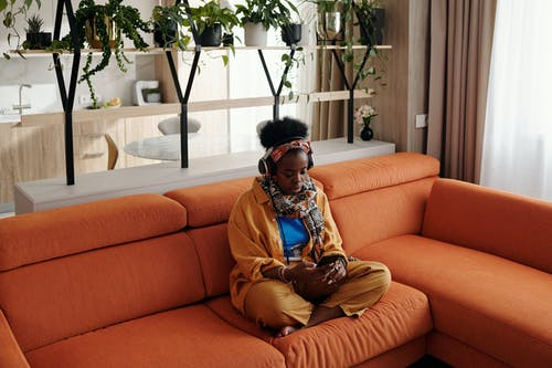 Woman in Brown Long Sleeve Shirt Sitting on Orange Couch