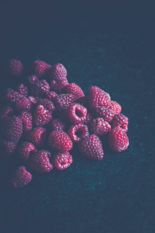 Red Raspberry Fruits on Blue Surface