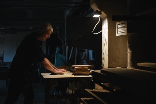 Side view of skilled male master processing wooden board while working at workbench in dark workshop with glowing lamp