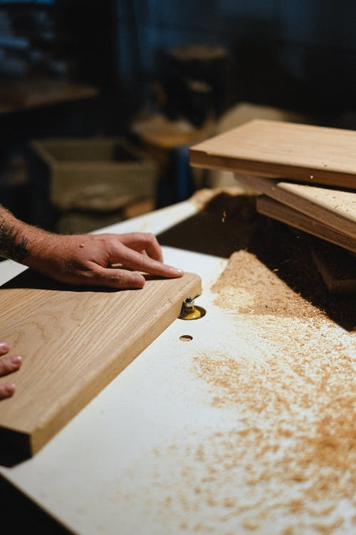 Crop carpenter shaping wooden board at router table