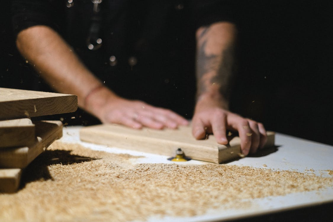 Unrecognizable male master standing at router table while shaping wooden plank at workbench with shavings in dark carpentry on blurred background