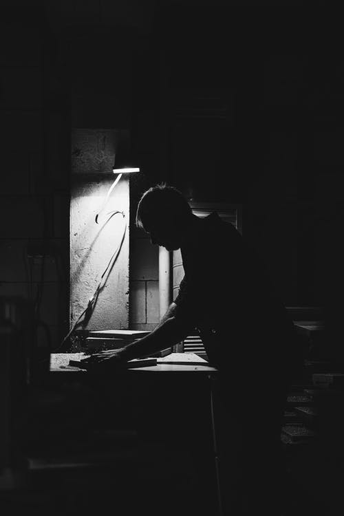 Black and white side view of anonymous male master standing at router table while shaping wooden detail in professional joinery