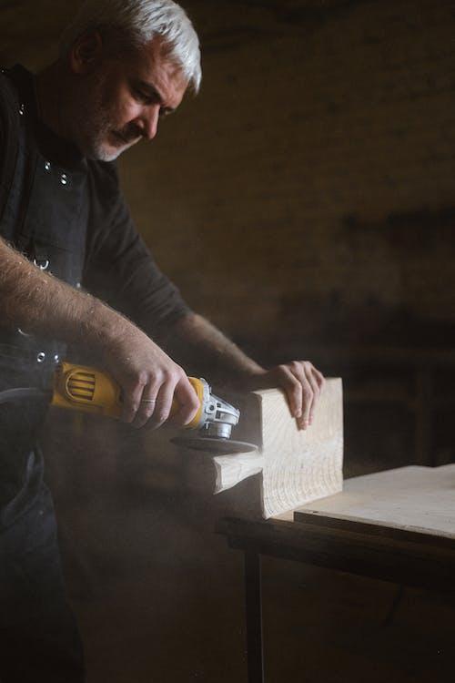 Focused craftsman using angle grinder