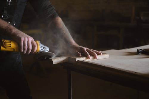 Unrecognizable male master using electric angle grinder to polish lumber plank while standing at table in professional joinery during work