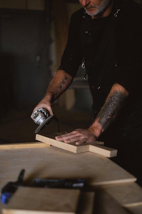 Crop woodworker grinding wooden plank