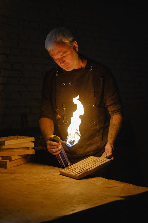 Serious male master in apron burning wooden board with creative pattern while standing at table in dark professional workshop with flame