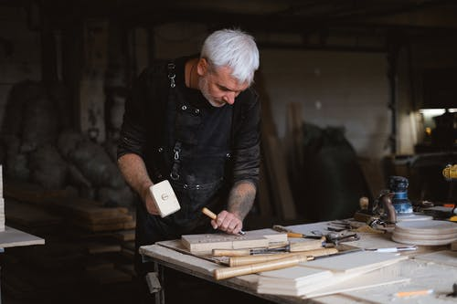 Serious male woodworker in apron using mallet and chisel to carve wooden board at table with abundance of instruments in carpentry