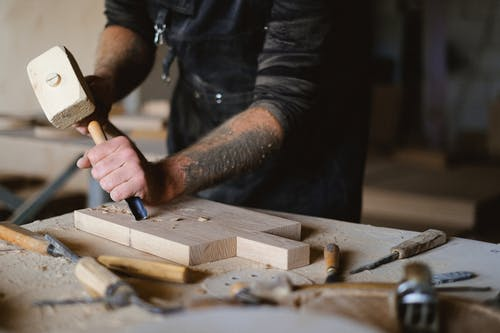 Unrecognizable male carpenter using forged chisel and wooden hammer while creating pattern on lumber board at table in workshop on blurred background