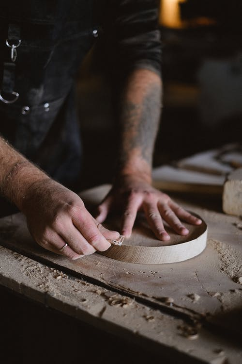 Person Holding Brown Wooden Round Board