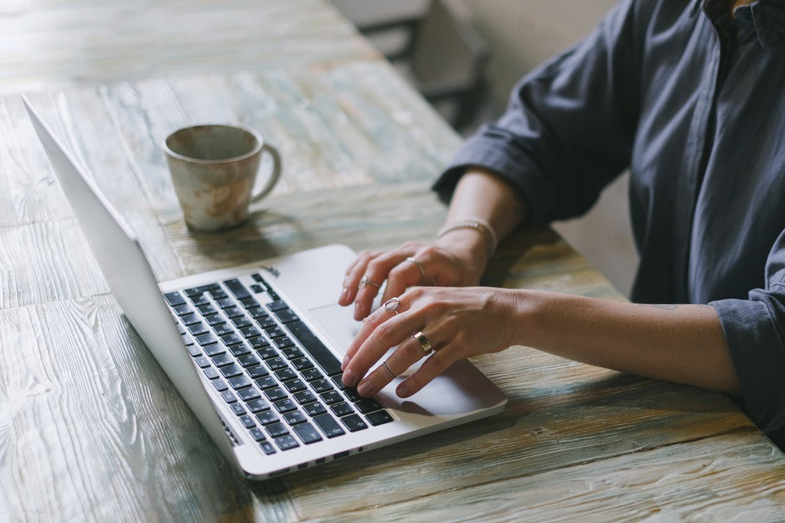 Crop faceless female freelancer in casual outfit sitting at table with cup of drink and surfing on laptop in light workspace