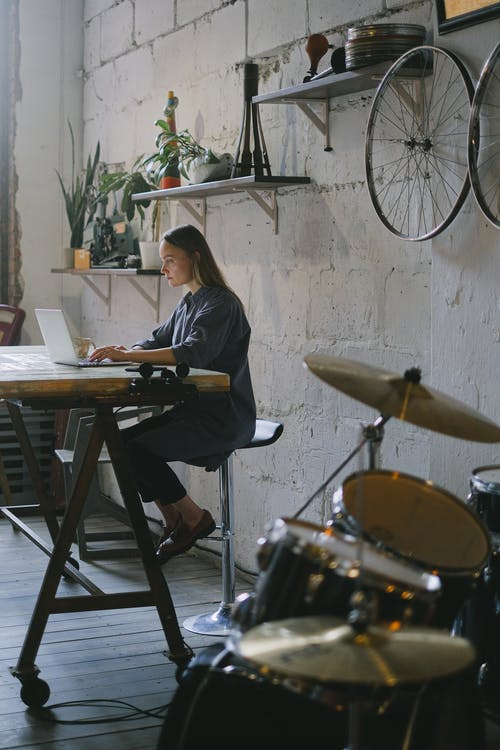 Side view of focused female freelancer wearing casual clothes sitting and typing on modern laptop in creative room with drums