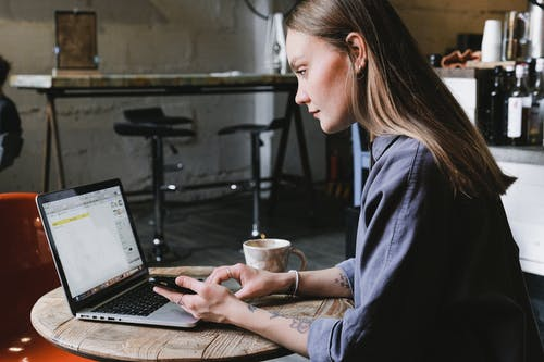 Side view of young focused woman browsing laptop sitting at table with cup of hot beverage in cafe
