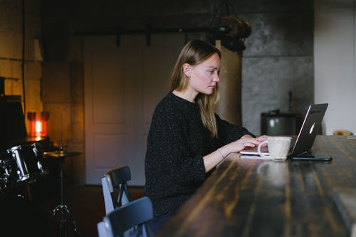 Side view of young woman working on netbook sitting at table with cup of hot beverage in kitchen