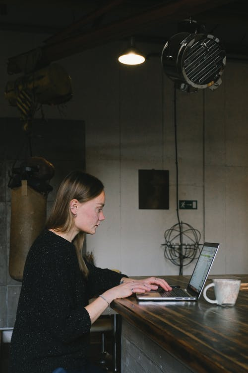 Side view of concentrated female freelancer surfing netbook while sitting at wooden table with cup of coffee during remote work