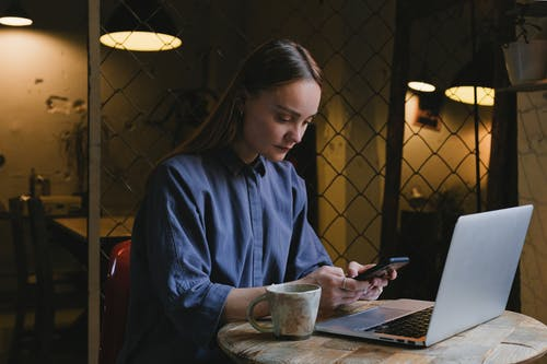 Focused woman messaging on smartphone at table in cafe