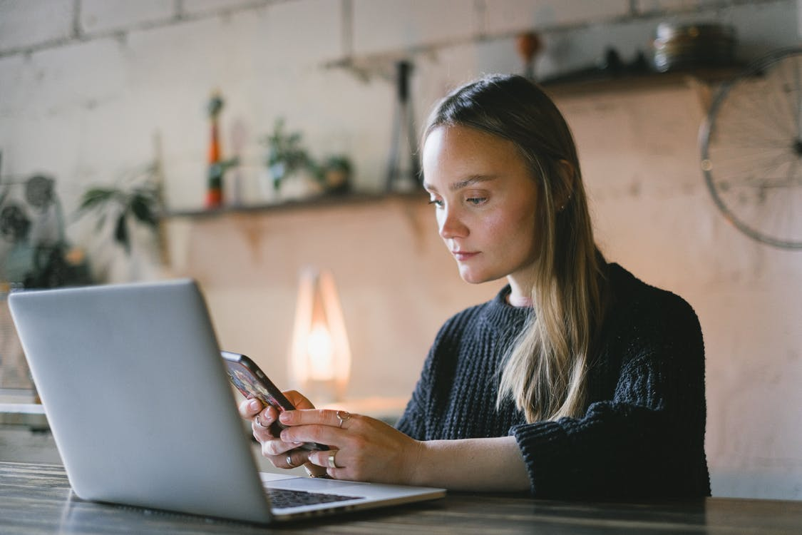 Concentrated female freelancer text messaging on cellphone while sitting at table with netbook during online work on blurred background