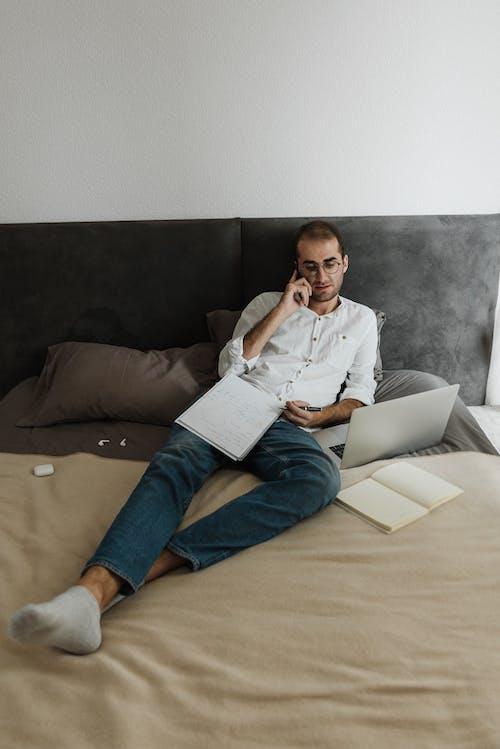 白色禮服襯衫和藍色牛仔牛仔褲,坐在棕色的沙發上的男人