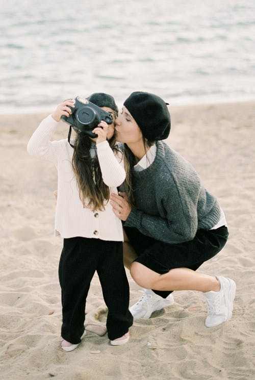Mother Kissing Her Child on the Beach