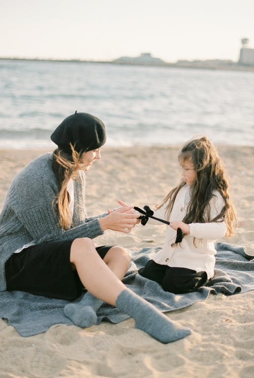 Mother and Daughter Sitting on the Sand