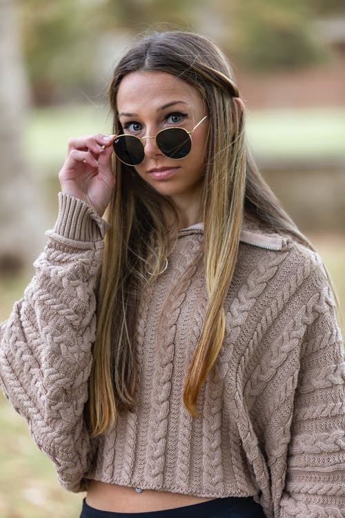 Stylish young woman in fashionable sunglasses and knitted sweater