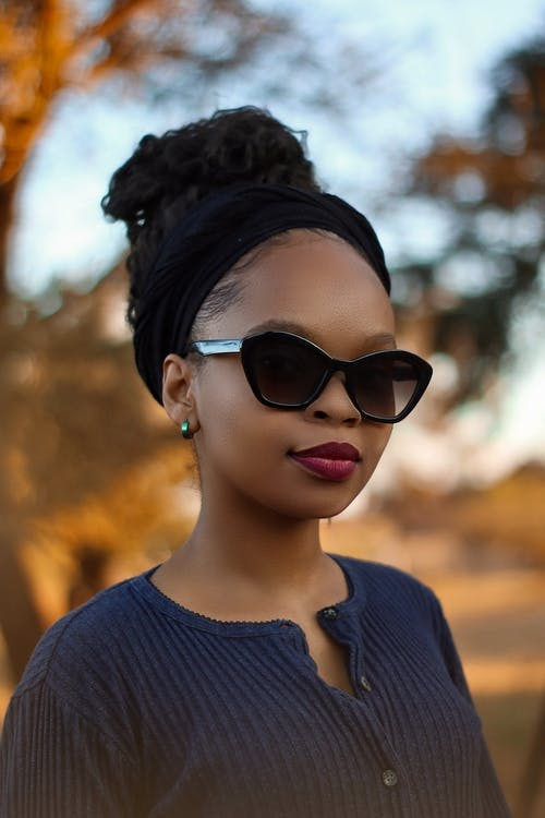Charming black woman in sunglasses standing against trees