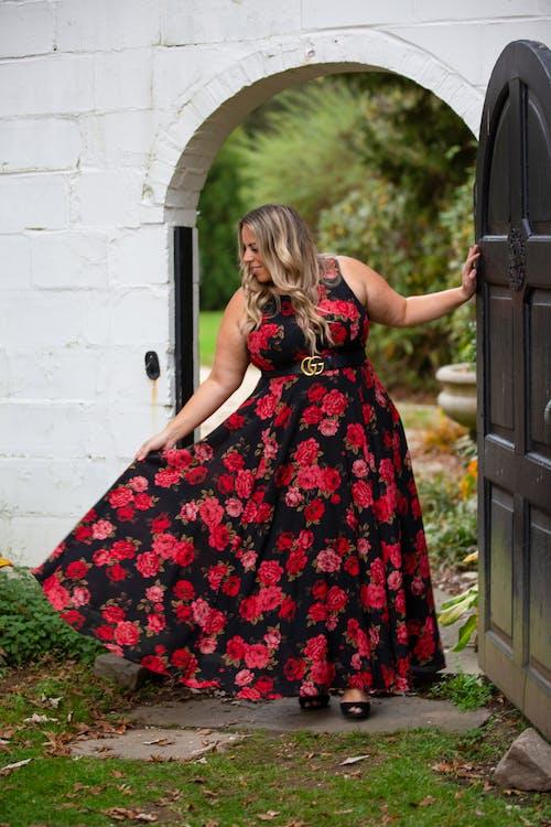 Elegant positive woman in bright stylish dress near door