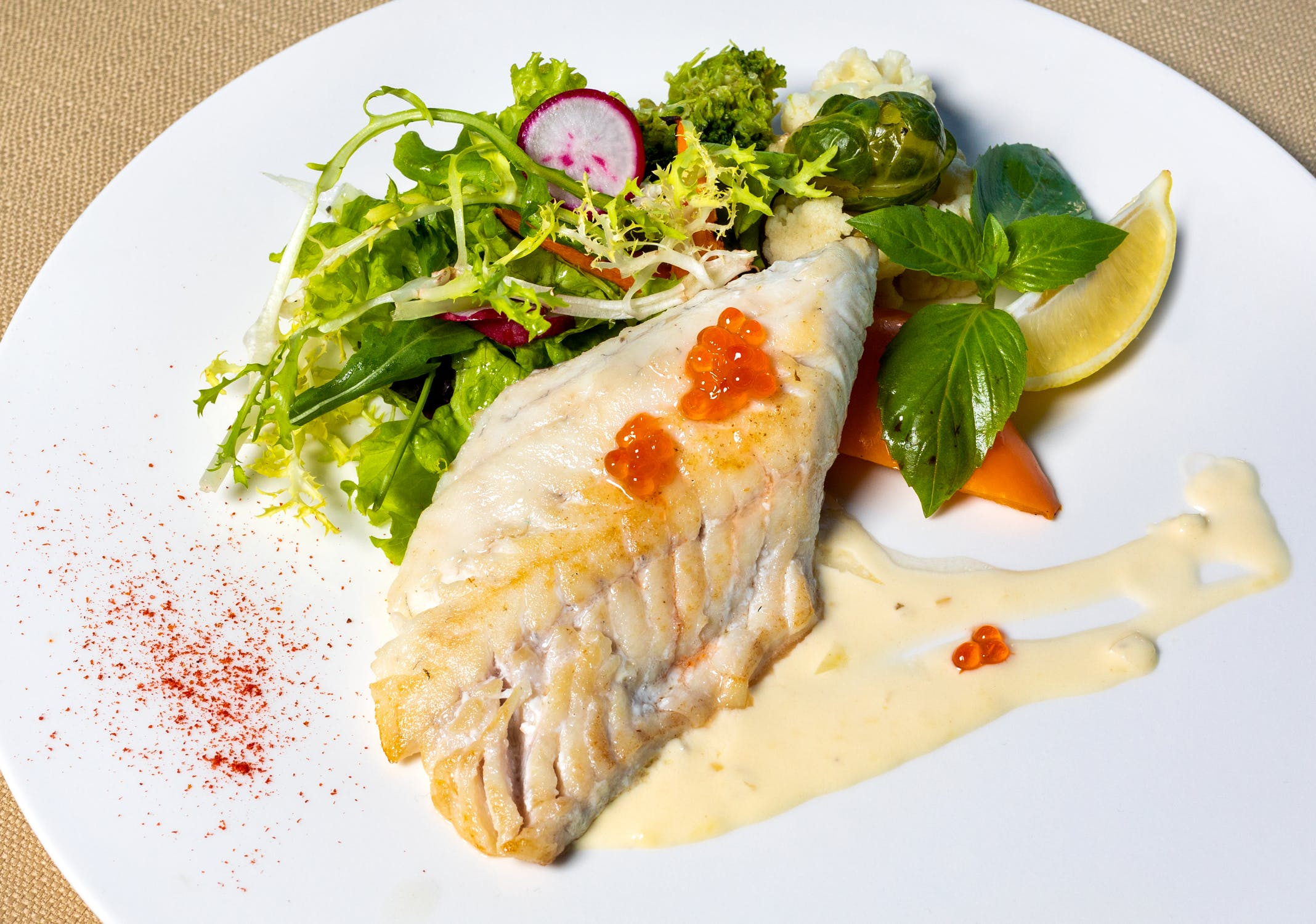 cod on a plate with salad and fish eggs.