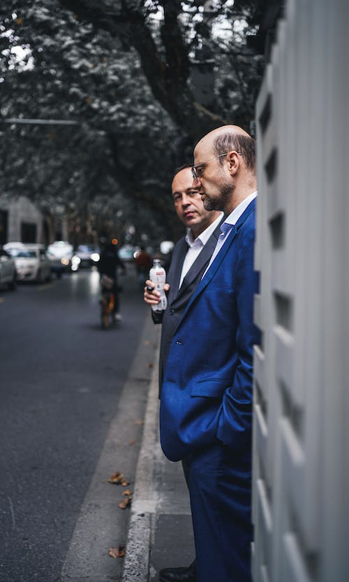 Serious businessmen in suit standing on sidewalk