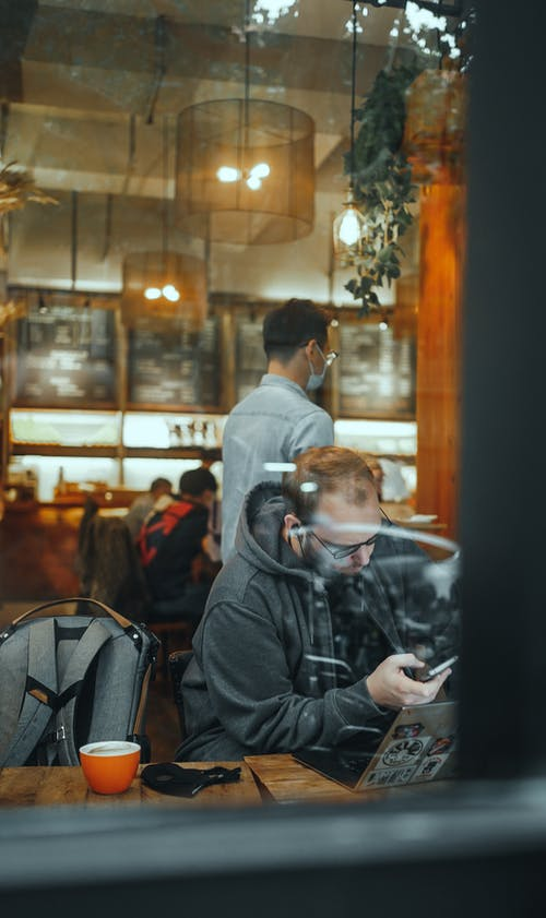 Through glass of focused male freelancer scrolling mobile phone while working in cozy cafe during coronavirus pandemic
