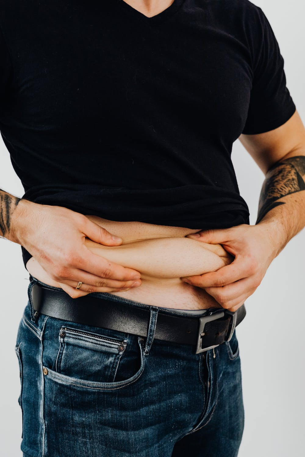 Man in black crew neck t-shirt holding his big belly.   Photo: Pexels
