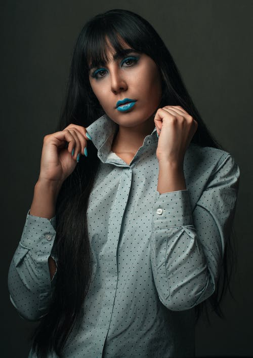 Young woman with long hair wearing blue lipstick and trendy shirt looking at camera