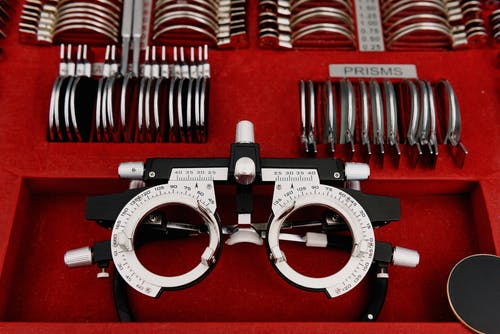 High angle collection of various trial lenses and frame placed in red holder in ophthalmology clinic