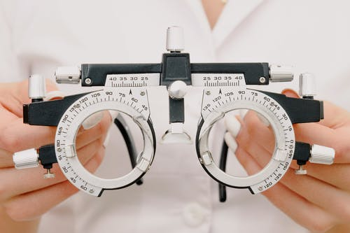 Crop anonymous female optometrist wearing medical robe holding modern trial frame with lenses in hands in modern optometry clinic