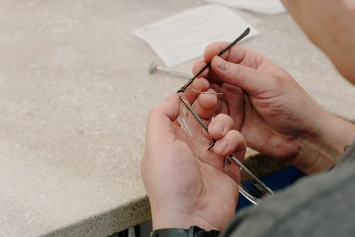 Crop man fixing broken eyeglasses