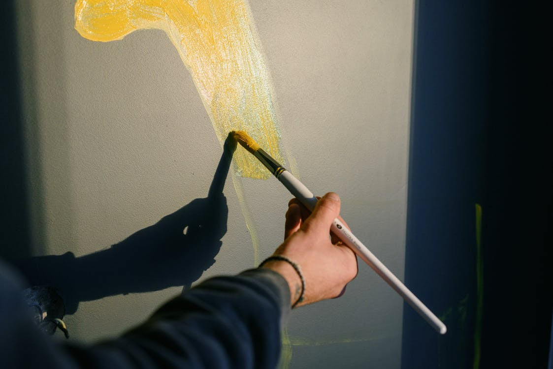 Unrecognizable professional male painter drawing yellow gouache with paintbrush in sunlight while casting shadow on black wall while creating artwork
