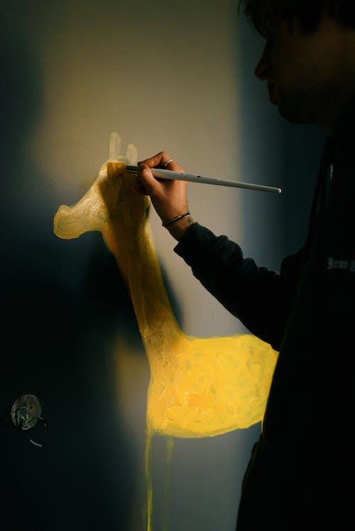 Side view crop male in workwear drawing yellow animal on dark wall in kid bedroom