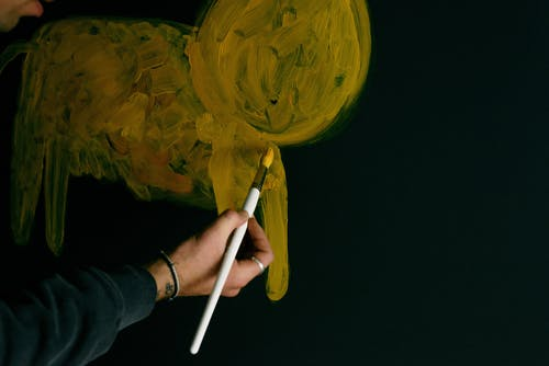 Crop unrecognizable person artist in gray sweater with paintbrush drawing abstract animal with yellow paints on dark wall