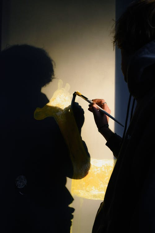Back view crop talented artist drawing animal with yellow paints on dark wall in new apartment