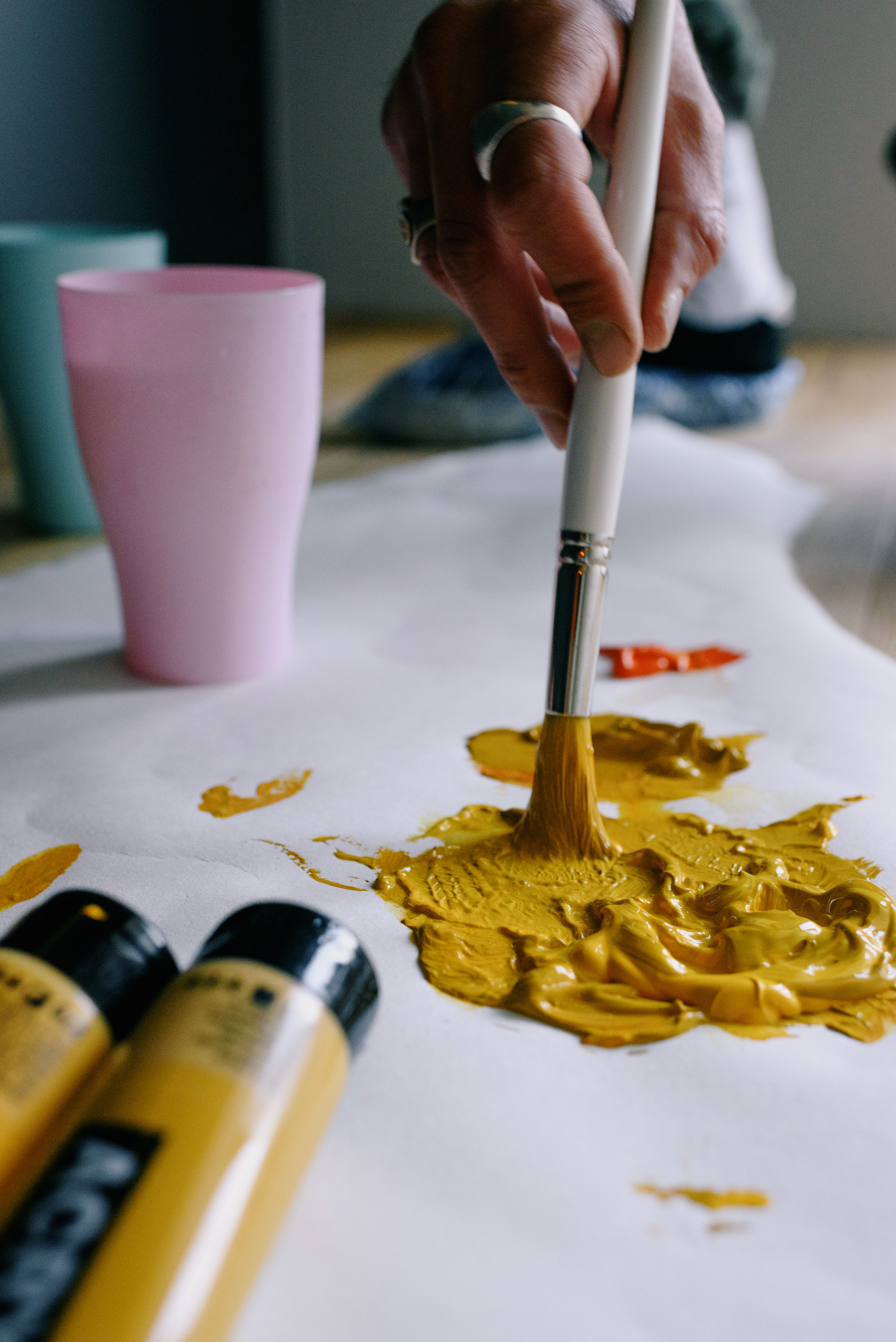 crop faceless artist sopping paintbrush in yellow paint