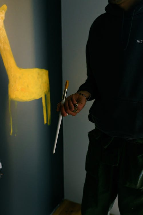 Crop anonymous male painter in casual clothes standing with paintbrush near dark wall and painting yellow animal in new apartment