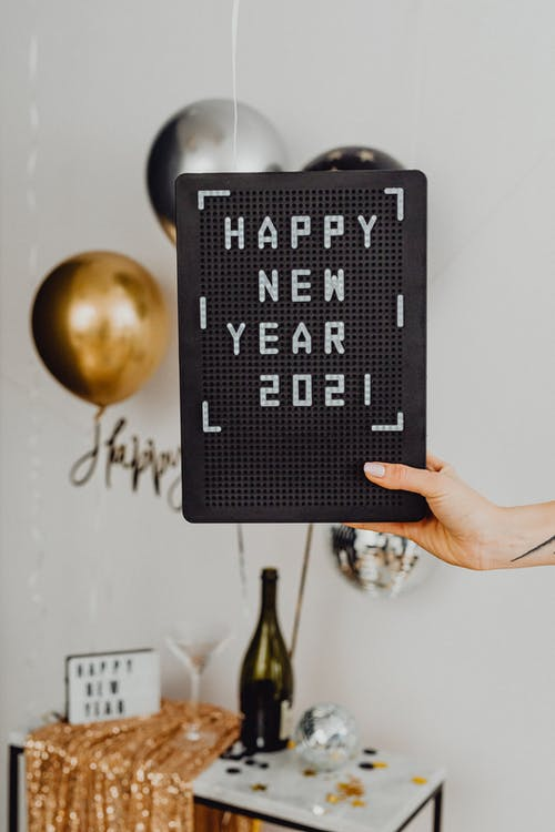 Person Holding A Happy New Year Text On A Black Board