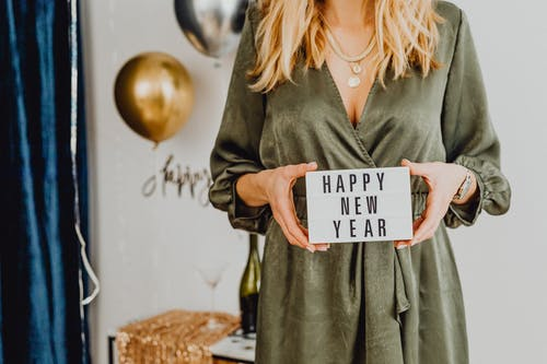Woman Holding White Card With Happy New Year Text