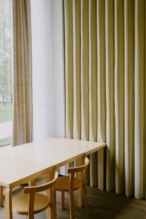 Table with chairs and curtains near window