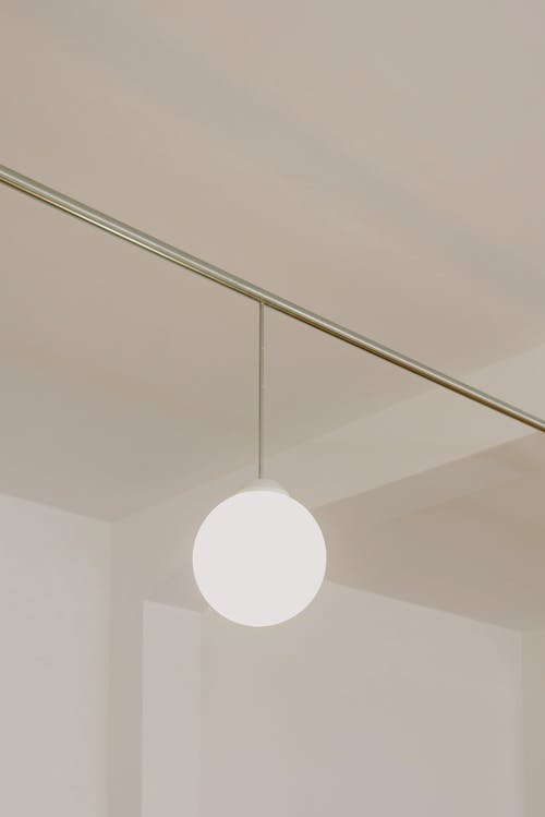 From below of round lamp hanging on ceiling of residential building with white walls