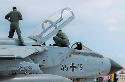 Low angle of unrecognizable male pilots in uniforms standing on aged gray multirole combat aircraft before flight against cloudy sunset sky