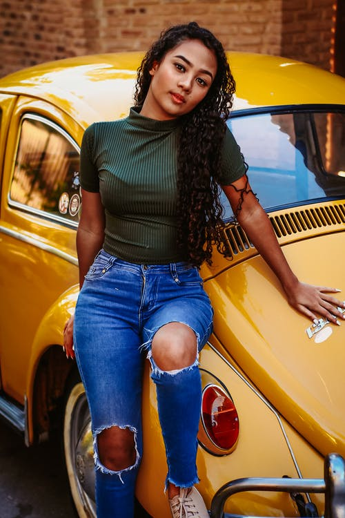Woman in Green Shirt and Blue Denim Jeans Standing Beside Yellow Car